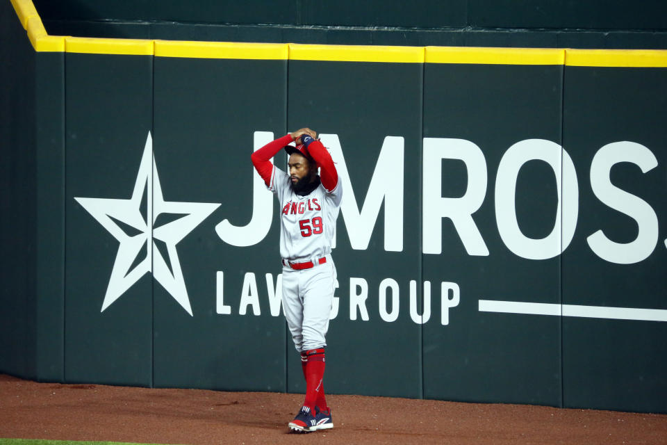 Los Angeles Angels right fielder Jo Adell puts his hands on his head after a fly ball by Texas Rangers' Nick Solak popped out of his glove and over the right field wall for a solo home run during the fifth inning of a baseball game in Arlington, Texas, Sunday, Aug. 9, 2020. (AP Photo/Ray Carlin)