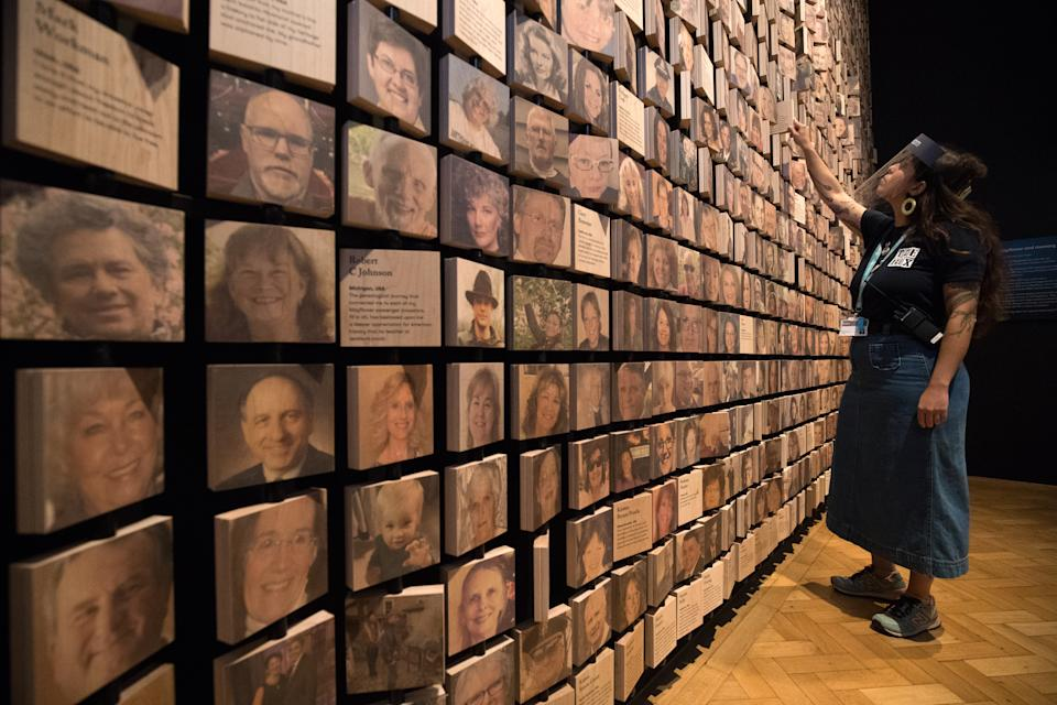 A staff member looks at a wall of faces of descendants related to the Mayflower, which part of the Mayflower 400: Legend and Legacy exhibition, during a press preview for the UK's largest ever commemorative exhibition on the Mayflower, with works on loan from both Smithsonian and Peabody institutes in America, at The Box museum in Plymouth, Devon. (Photo by Andrew Matthews/PA Images via Getty Images)