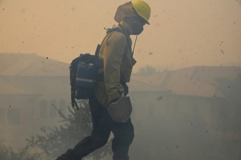 Orange County firefighter John Nelson looks for hot spots as driving winds propel ash and particles through the air near a residential community in the Silverado Fire October 26, 2020 in Irvine, California
