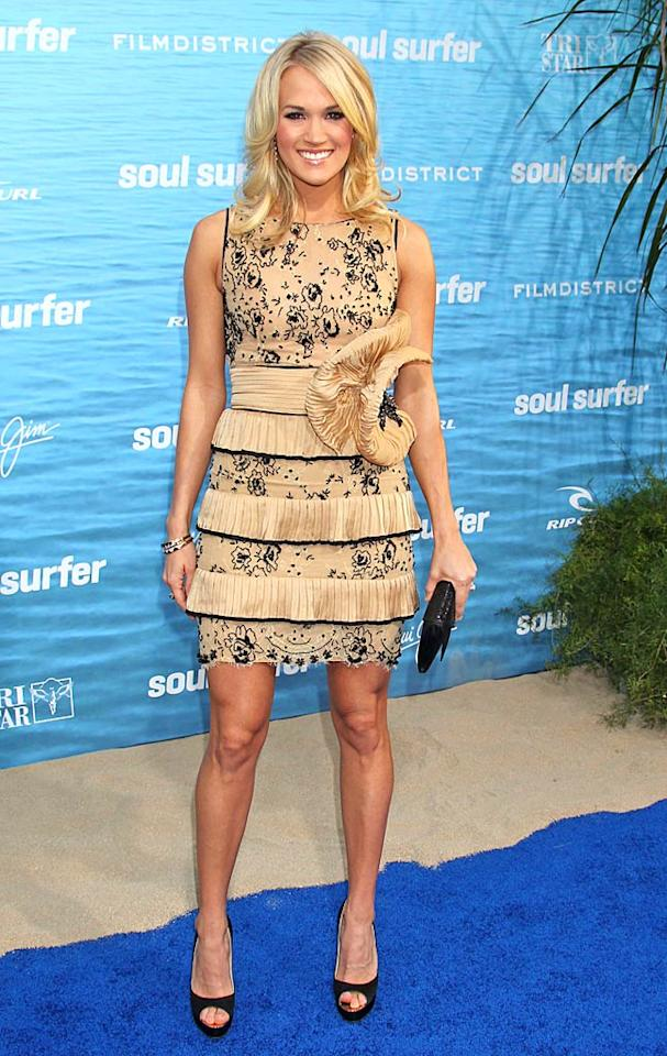 "Carrie Underwood took a fashion risk (that totally paid off) by donning an interesting dress to the L.A. premiere of ""Soul Surfer."" The country cutie turned heads in Brian Atwood peep-toes, gold bangles, and a marvelous Zuhair Murad frock, which featured a tiered skirt, black lace detailing, and a floral accent on the waist. Russ Einhorn/<a href=""http://www.splashnewsonline.com"" target=""new"">Splash News</a> - March 30, 2011"