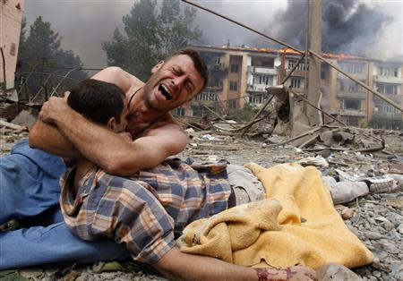 A Georgian man cries as he holds the body of his relative after a bombardment in Gori, 80 km (50 miles) from Tbilisi, in this August 9, 2008 file photo. REUTERS/Gleb Garanich/Files