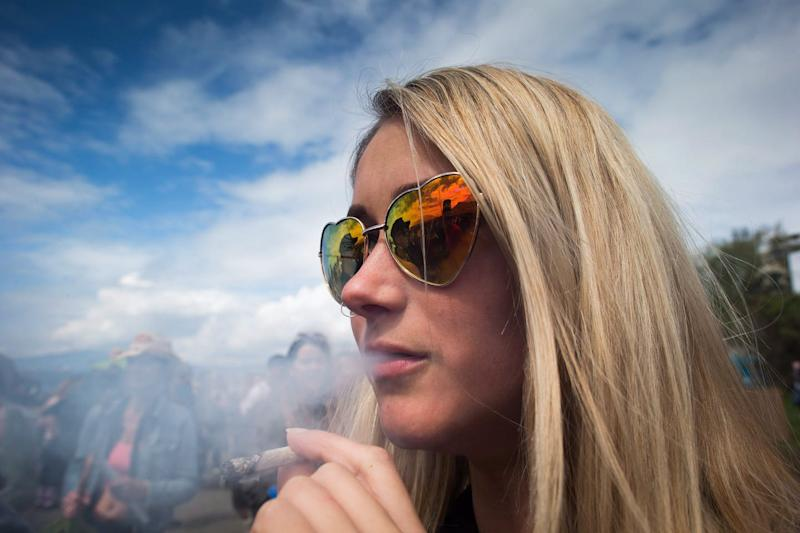 A blonde woman wearing heart-shaped sunglasses smoking a joint at an outdoor event.