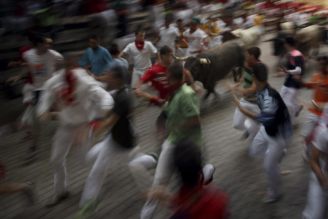 <p>Revelers run alongside the daily running of the bulls of the San Fermin festival in Pamplona, Spain, July 14, 2015. (Photo: Daniel Ochoa de Olza/AP) </p>