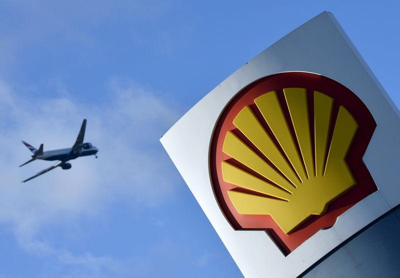 FILE PHOTO: File photo of passenger plane flies over a Shell logo at a petrol station in west London