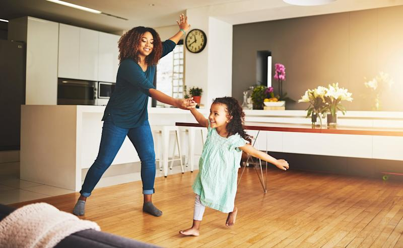 Shot of a little girl and her mother dancing at home