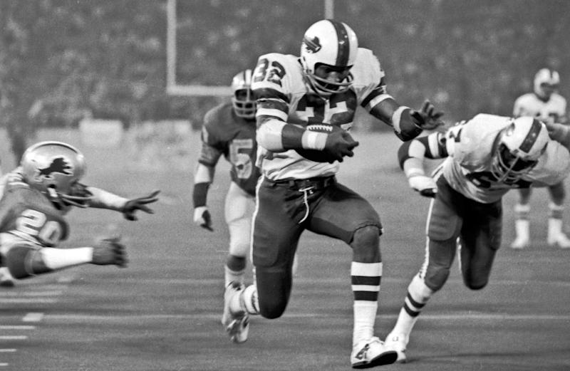 """FILE - In this Nov. 25, 1976 file photo, Buffalo Bills' O.J. Simpson rushes through a large hole in the center fo the Detroit Lions defensive line to score on a 12-yard run for his second touchdown of the game in an NFL football game in Pontiac, Mich. Simpson added some """"Juice"""" - rushing for a Thanksgiving Day-record 273 yards - to what wound up as a 27-14 Bills defeat at the hands of the Lions at the Pontiac Silverdome on Thanksgiving Day 1976. (AP Photo/File)"""