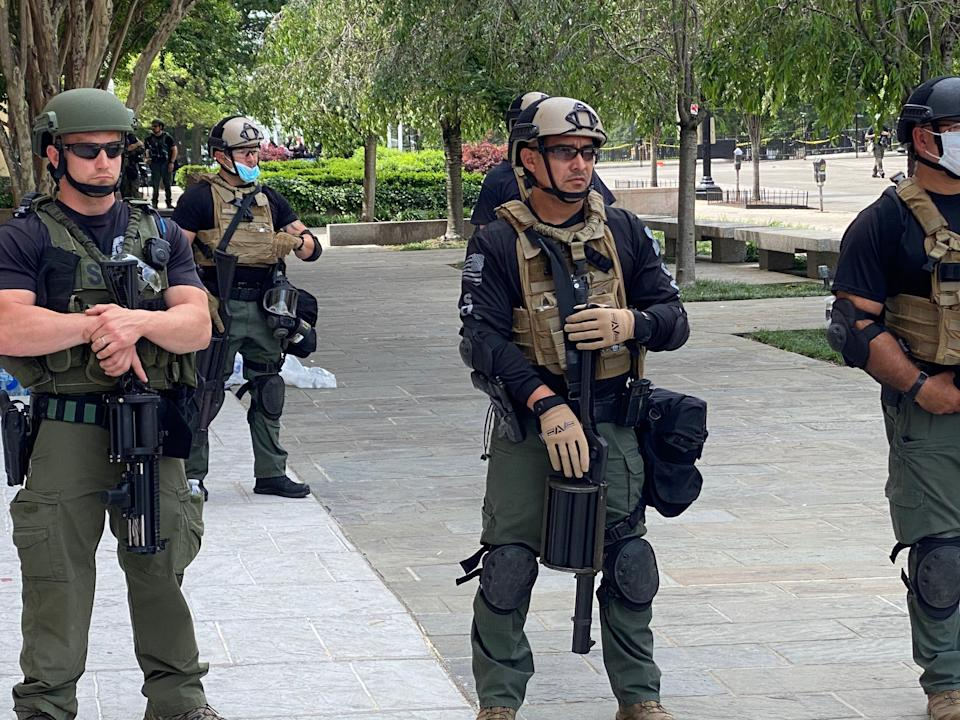 Federal law enforcement officers wear unidentifiable uniforms, some with plain T-shirts under their military-style gear, while they hold a line near the White House on Wednesday. (Photo: Ryan J. Reilly/HuffPost)
