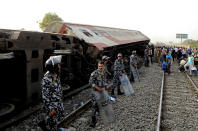 Security forces stand guard as people gather at the site where a passenger train derailed injuring at least 100 people, near Banha, Qalyubia province, Egypt, Sunday, April 18, 2021. At least eight train wagons ran off the railway, the provincial governor's office said in a statement. (AP Photo/Tarek Wagih)
