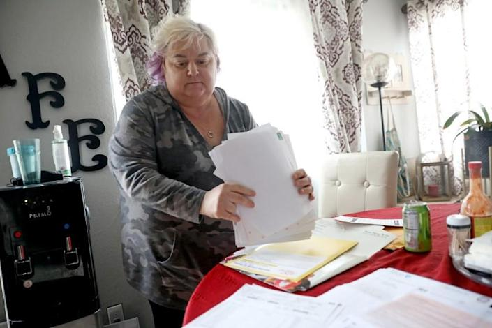 VACAVILLE, CA - JANUARY 26: Patricia Mason, 51, displays her medical bills at her home on Tuesday, Jan. 26, 2021 in Vacaville, CA. Mason works more than full time over two separate jobs - office administrative work, which she can do at home, and retail, which she can't. Patricia was hospitalized with COVID-19 from March 27 - April 20th of 2020 at NorthBay Medical Center. Her medical bill totaled $1,339,079, which her insurance covered most of it. But she still owes $42,184, which insurance won't cover, and it's gone to collections. (Gary Coronado / Los Angeles Times)