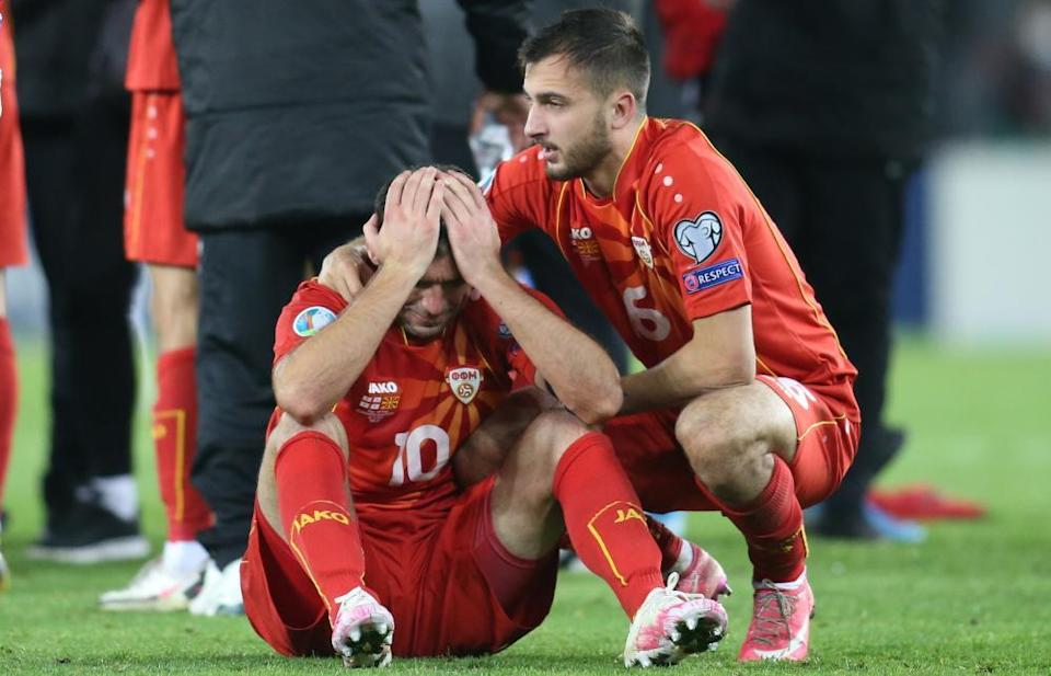 Goran Pandev, overcome by emotion, is comforted by a teammate Boban Nikolov after Pandev's goal against Georgia took North Macedonia to Euro 2020