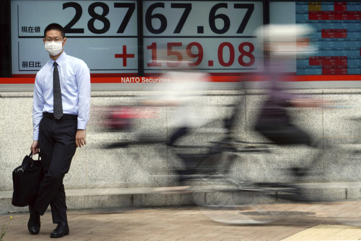 A man wearing a protective mask stands in front of an electronic stock board showing Japan's Nikkei 225 index at a securities firm Wednesday, May 12, 2021, in Tokyo. Asian stock markets retreated Wednesday as investors looked ahead to U.S. data they worry will show inflation is picking up. (AP Photo/Eugene Hoshiko)