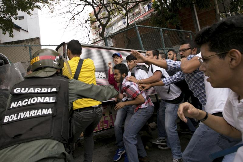 Venezuelan Bolivarian National guards officers are confronted by university students during a protest outside of the Supreme Court in Caracas, Venezuela, Friday, March 31, 2017. Venezuelans have been thrust into a new round of political turbulence after the government-stacked Supreme Court gutted congress of its last vestiges of power, drawing widespread condemnation from foreign governments and sparking protests in the capital. (AP Photo/Ariana Cubillos)