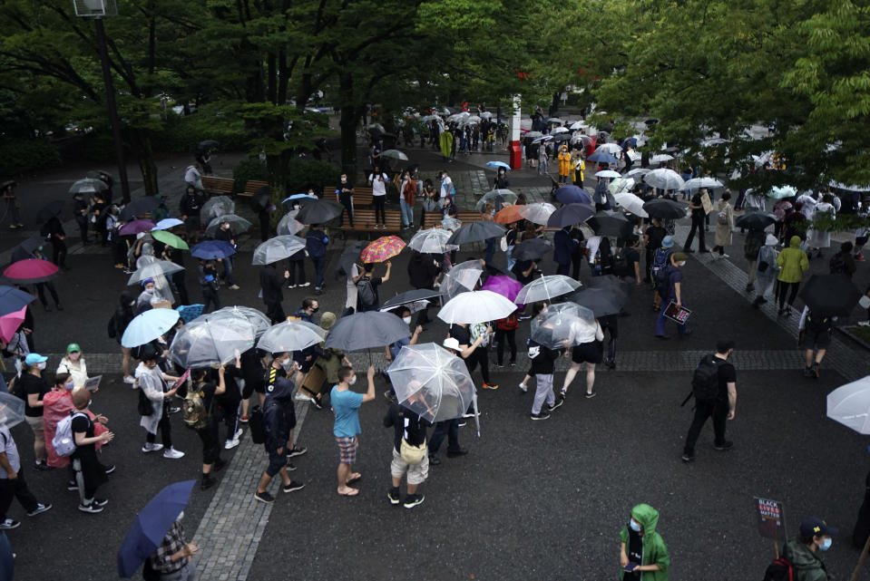 People march in the rain to protest during a solidarity rally for the death of George Floyd in Tokyo Sunday, June 14, 2020. Floyd died after being restrained by Minneapolis police officers on May 25. (AP Photo/Eugene Hoshiko)