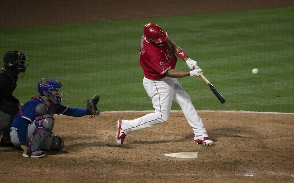 Angels' Albert Pujols hits a solo home run as Texas Rangers catcher Jose Trevino watches.