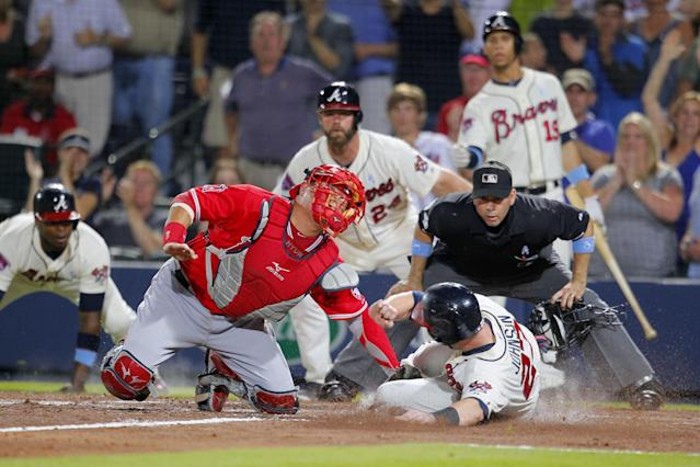 Los Angeles Angels catcher Hank Conger (16) tags out Atlanta Braves Chris Johnson (23) at the plate after Tommy La Stella brings in two runs in the sixth inning of an interleague baseball game Sunday, June 15, 2014, in Atlanta. (AP Photo/Todd Kirkland)