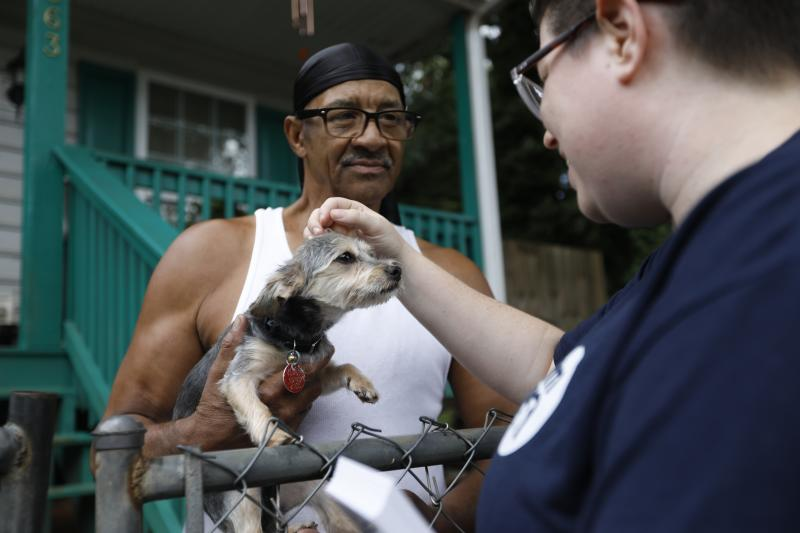 In this Tuesday, Aug. 27, 2019 photo, Sylvanus Jackson brings his dog out to meet Lizzy Trawick, a coordinator for LifeLine Animal Project's Pets for Life program in Atlanta. Trawick visited Jackson's neighborhood to complete door-to-door outreach for the program, which provides free resources to pet owners in need. Jackson said he has benefitted from the program and thanked the representatives who visited. (AP Photo/Andrea Smith)