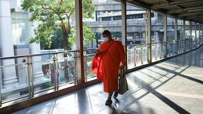 A monk wearing protective face mask walks a past skywalk amid a new wave of Covid-19 infections in Bangkok,