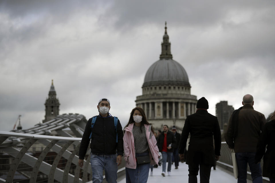 """People wearing face masks walk across the Millennium footbridge backdropped by the dome of St Paul's Cathedral in London, Tuesday, March 10, 2020. Starkly illustrating the global east-to-west spread of the new coronavirus, Italy began an extraordinary, sweeping nationwide travel ban on Tuesday while in China, the diminishing threat prompted the president to visit the epicenter and declare: """"""""We will certainly defeat this epidemic."""" (AP Photo/Matt Dunham)"""