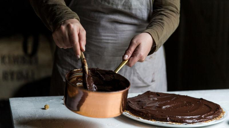 Two hands stirring a copper pot of melted chocolate being used to top a tart