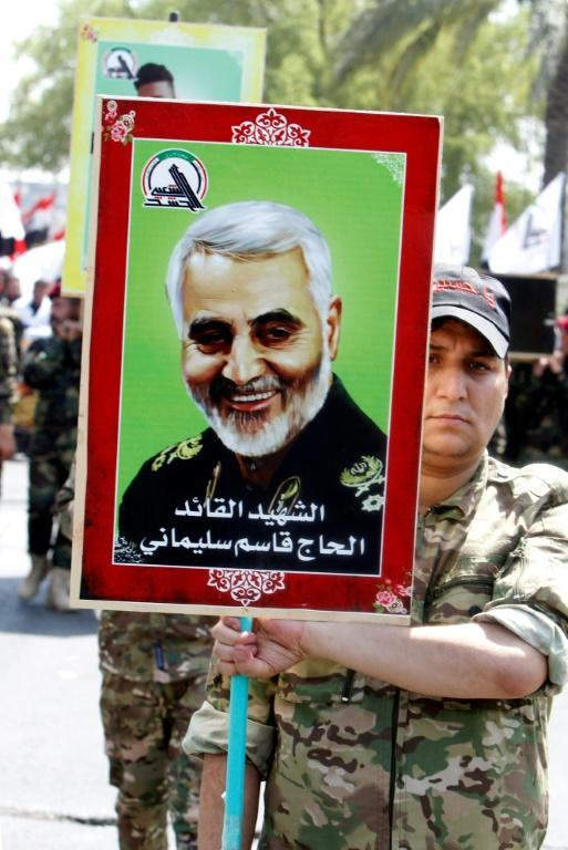 A member of Iraq's Hashed al-Shaabi paramilitary forces marches with a portrait of slain Iranian Revolutionary Guards commander Qasem Soleimani in Baghdad on June 29