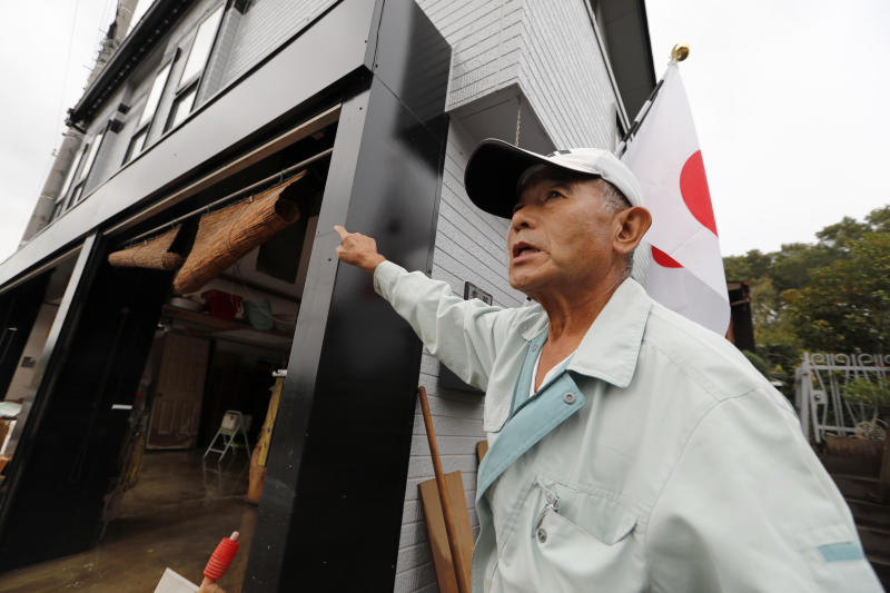 CORRECTS NAME - Kazuo Saito shows the flood water level of his house as he cleans up Monday, Oct. 14, 2019, in Kawagoe City, Japan. Typhoon Hagibis dropped record amounts of rain for a period in some spots, according to meteorological officials, causing more than 20 rivers to overflow. Some of the muddy waters in streets, fields and residential areas have subsided. But many places remained flooded, with homes and surrounding roads covered in mud and littered with broken wooden pieces and debris. (AP Photo/Eugene Hoshiko)