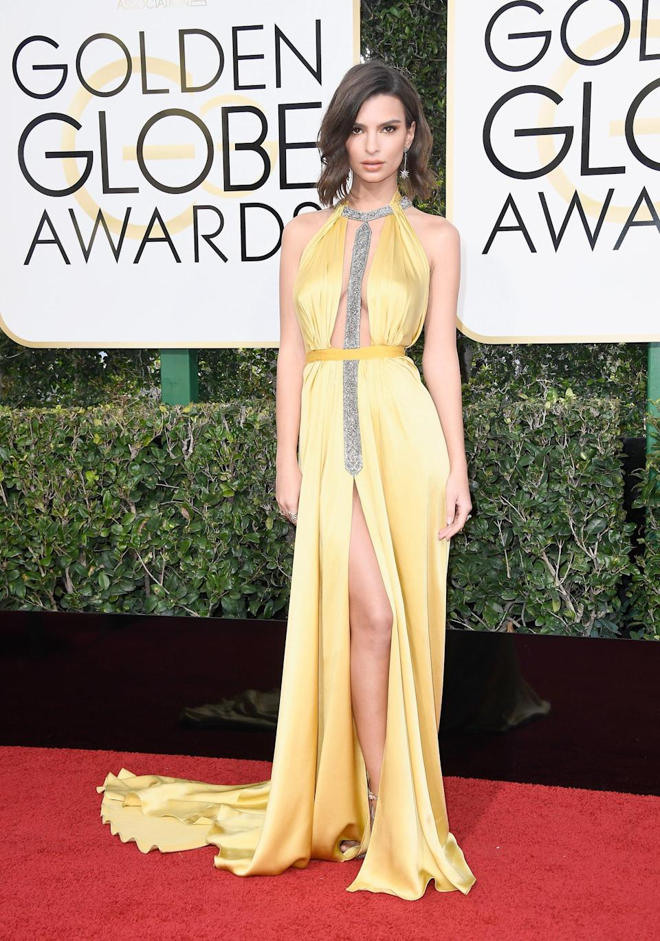 <p>Emily wore a gold cutout Reem Acra gown, Stuart Weitzman heels, and H. Stern 18k gold earrings to the 2017 Golden Globe Awards.</p>