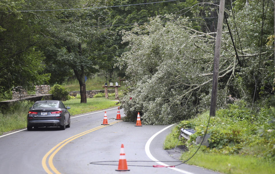 A vehicle has to maneuver around a downed tree across a power line on Route 138 in South Kingstown, R.I., Sunday, Aug. 22, 2021. Strong winds from Tropical Storm Henri toppled many trees in the southern regional of the state. (AP Photo/Stew Milne)