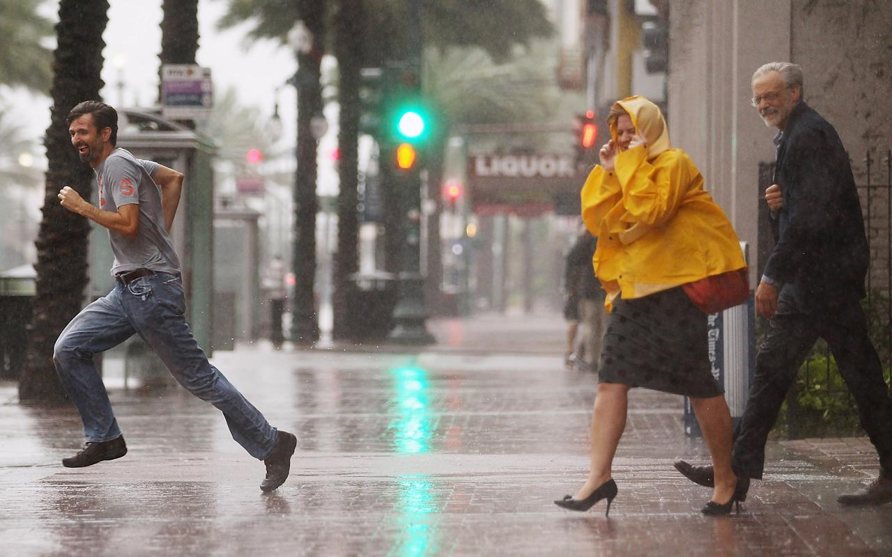 NEW ORLEANS, LA - AUGUST 28:  People make their way across Canal Street on August 28, 2012 in New Orleans, Louisiana. New Orleans is bracing for the approach of Hurricane Isaac, now a Category 1 storm, which is predicted to hit the city on August 29, the seventh anniversary of Hurricane Katrina.   (Photo by Mario Tama/Getty Images)