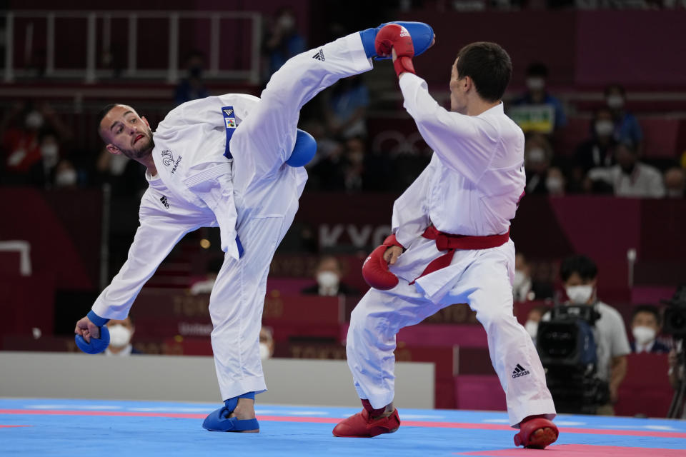 Darkhan Assadilov of Kazakhstan, right, and Steven da Costa of France compete in the men's kumite -67kg semifinal bout for Karate at the 2020 Summer Olympics, Thursday, Aug. 5, 2021, in Tokyo, Japan. (AP Photo/Vincent Thian)