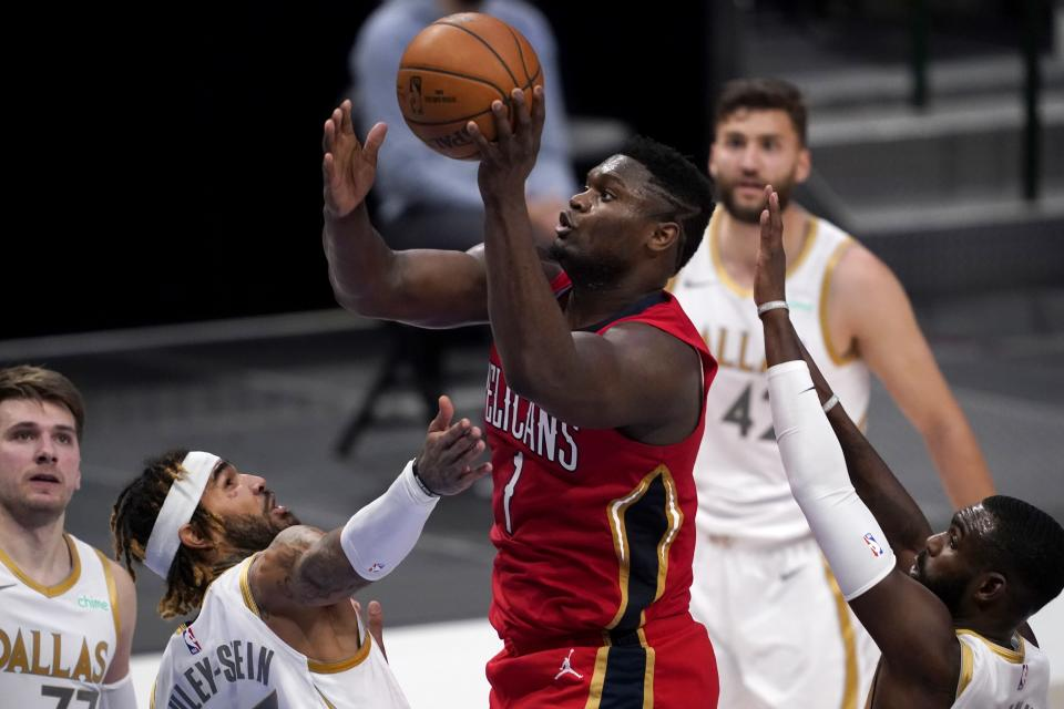 New Orleans Pelicans forward Zion Williamson (1) shoots between Dallas Mavericks' Willie Cauley-Stein and Tim Hardaway Jr., right, as Luka Doncic, left rear, and Maxi Kleber, right rear, watches during the second half of an NBA basketball game in Dallas, Friday, Feb. 12, 2021. (AP Photo/Tony Gutierrez)