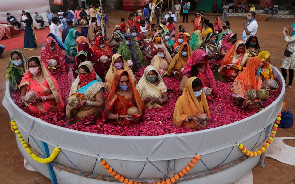 Indian women perform rituals inside an artificial pond on Chhat Puja festival in Mumbai - Rajanish Kakade/AP