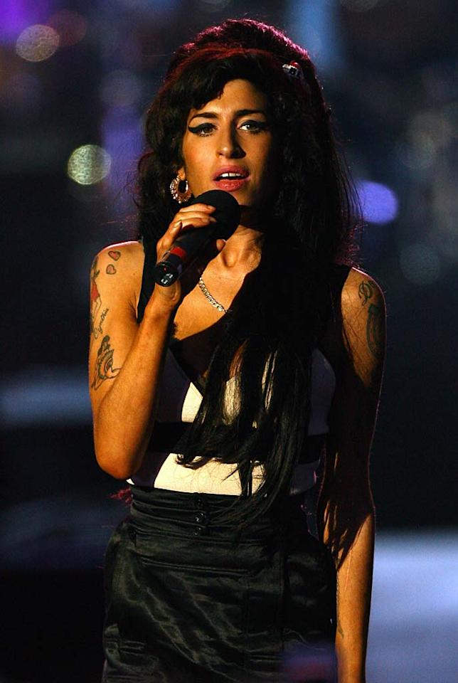 "Amy Winehouse returned to the stage Friday night, where she sang for Nelson Mandela's 90th birthday concert. It was her first public appearance and performance since last week's hospitalization and reports from her father that the British singer had ""traces"" of emphysema. Gareth Cattermole/<a href=""http://www.gettyimages.com/"" target=""new"">GettyImages.com</a> - June 27, 2008"