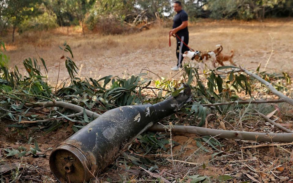 An Israeli man walks past the remains of a rocket fire by the Palestinian Islamist group Hamas from the Gaza Strip