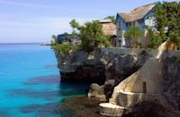 """<p>Owned by Island Outpost, the boutique luxury hospitality brand that owns GoldenEye and Fleming Villa, the Caves Hotel is a unique all-inclusive experience from the others on the island. It only houses 12 accommodations, all of which are cliffside cottages, plus intimate coral stairways, nooks, and coves for exploring. </p><p>""""<a href=""""https://www.thecaveshotel.com/"""" rel=""""nofollow noopener"""" target=""""_blank"""" data-ylk=""""slk:The Caves Hotel"""" class=""""link rapid-noclick-resp"""">The Caves Hotel</a> is for the traveler who hates large, all-inclusive resorts because they are too large to provide adequate quality services,"""" say the Joneses. """"The Caves doesn't sit on a popular beach. Instead, it's perched above the Caribbean Sea and bares a strong resemblance to Greece due to its white limestone structure. It's just a few minutes from the very popular seven-mile beach and a quick walk from the world-famous Rick's Café. This boutique resort is our favorite place in Jamaica."""" Plus, the resort boasts some of the best food on the island—and guests can take control of the bar once the staff goes home for the night. </p>"""