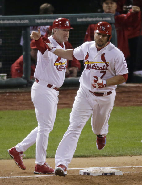 St. Louis Cardinals' Matt Holliday (7) is congratulated by first base coach Chris Maloney after Holiday hit a home run during the fourth inning of Game 5 of baseball's World Series against the Boston Red Sox Monday, Oct. 28, 2013, in St. Louis. (AP Photo/Charlie Riedel)