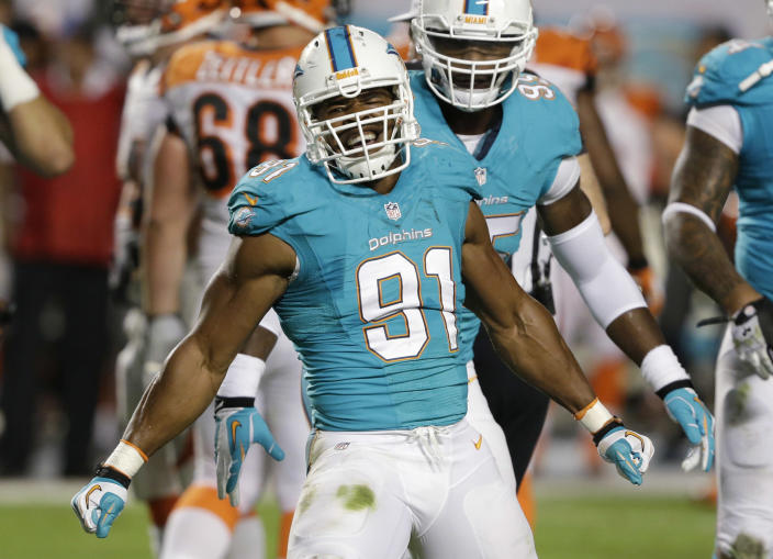 Miami Dolphins defensive end Cameron Wake celebrates after he recovered a fumble by Cincinnati Bengals quarterback Andy Dalton during the first half of an NFL football game, Thursday, Oct. 31, 2013, in Miami Gardens, Fla. (AP Photo/Wilfredo Lee)