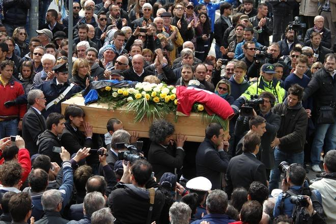 Family and friends of footballer Piermario Morosini follow his coffin after the funeral service at San Gregorio Barbarigo church on April 19, 2012 in Bergamo. The 25-year-old, who played for second division team Livorno and was on loan from Udinese, died during a match at Pescara on April 14. AFP PHOTO / GIUSEPPE CACACE  AFP PHOTO / POOL /PAOLO MAGNI