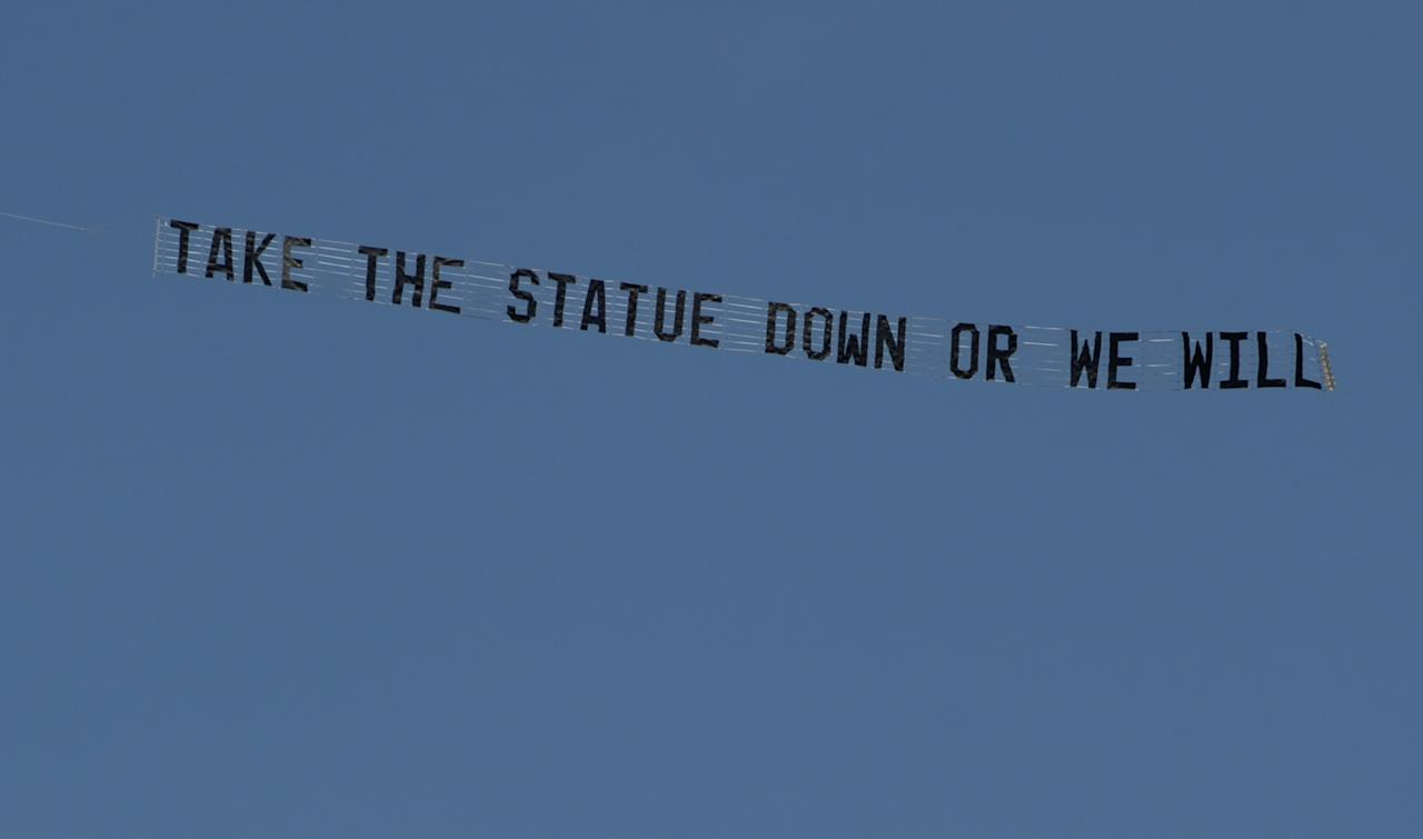 "A plane flying the Penn State University campus in State College, pulls a banner reading ""Take the statue down or we will"" on Tuesday, July 17, 2012. The Paterno statue outside Beaver Stadium has been a point of much contention. Critics have called for the statue to be taken down after the Freeh report concluded that Paterno was aware of a 1998 allegations against Sandusky _ in contrast to his grand jury testimony and an interview given after his firing _ and that he was involved in the decision to not report a 2001 incident to the authorities even after his superiors had decided to. (AP Photo/Centre Daily Times, Nabil K. Mark) MAGS OUT, MANDATORY CREDIT"