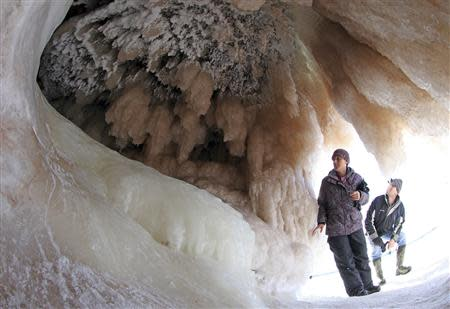 Sightseers look at ice formations in sea caves of the Apostle Islands National Lakeshore of Lake Superior near Cornucopia, Wisconsin February 14, 2014. REUTERS/Eric Miller