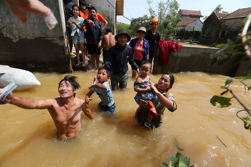 Residents get money from a volunteer at a flooded area in Quang Binh province