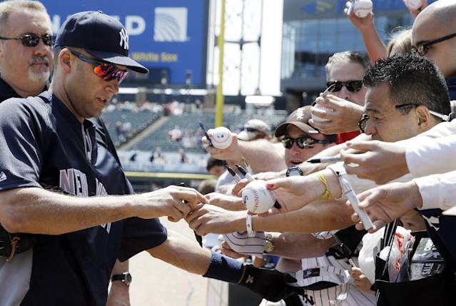 New York Yankees' Derek Jeter, left, signs autographs for fans before a baseball game against the Chicago White Sox in Chicago on Saturday, May 24, 2014. (AP Photo/Nam Y. Huh)