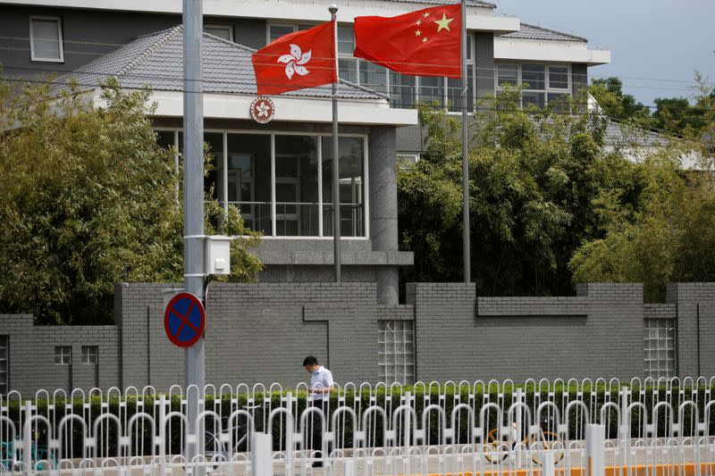 Man walks past Chinese and Hong Kong flags in Beijing