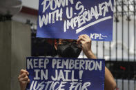 A protester holds a slogan during a rally outside the Department of Justice in Manila, Philippines on Thursday Sept. 3, 2020. A Philippine court has ordered the early release for good conduct of U.S. Marine Lance Cpl. Joseph Scott Pemberton convicted in the 2014 killing of transgender Filipino Jennifer Laude which sparked anger in the former American colony. (AP Photo/Aaron Favila)