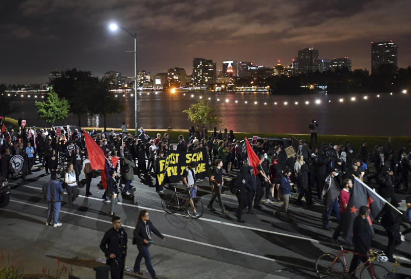 Several hundred protesters walk past Lake Merritt in Oakland, Calif., Saturday, Aug. 12, 2017. Protesters marche in Oakland to decry racism in the wake of deadly violence that erupted at a white nationalist demonstration in Virginia. (AP Photo/Noah Berger)