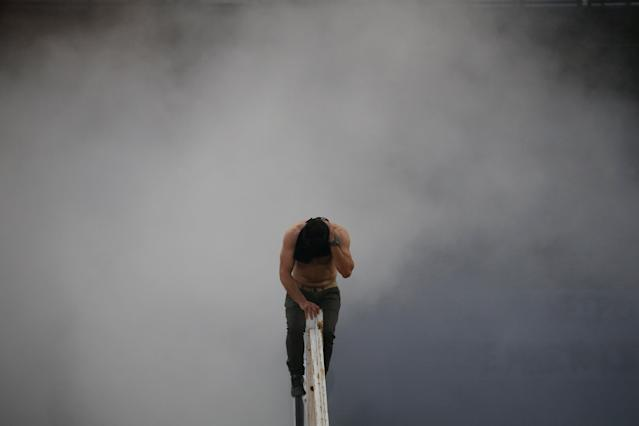 Soccer Football - Greek Cup Final - AEK Athens vs PAOK Salonika - Athens Olympic Stadium, Athens, Greece - May 12, 2018 A PAOK Salonika fan on a rail reacts to smoke before the match REUTERS/Alkis Konstantinidis