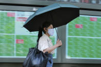 A woman walks by an electronic stock board of a securities firm in Tokyo, Wednesday, Sept. 15, 2021. Asian stock markets followed Wall Street down on Wednesday after U.S. inflation was lower than expected amid unease about the impact of the spread of the coronavirus's delta variant. (AP Photo/Koji Sasahara)