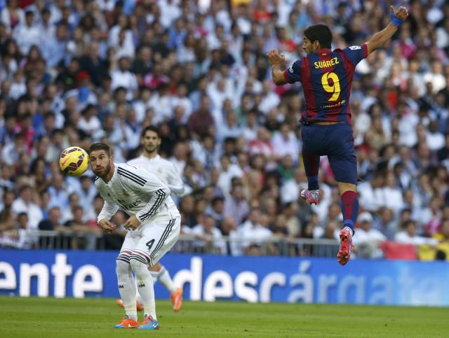 "Barcelona's Luis Suarez (R) heads the ball as Real Madrid's Sergio Ramos looks on during their Spanish first division ""Clasico"" soccer match at the Santiago Bernabeu stadium in Madrid October 25, 2014. REUTERS/Sergio Perez (SPAIN - Tags: SOCCER SPORT)"