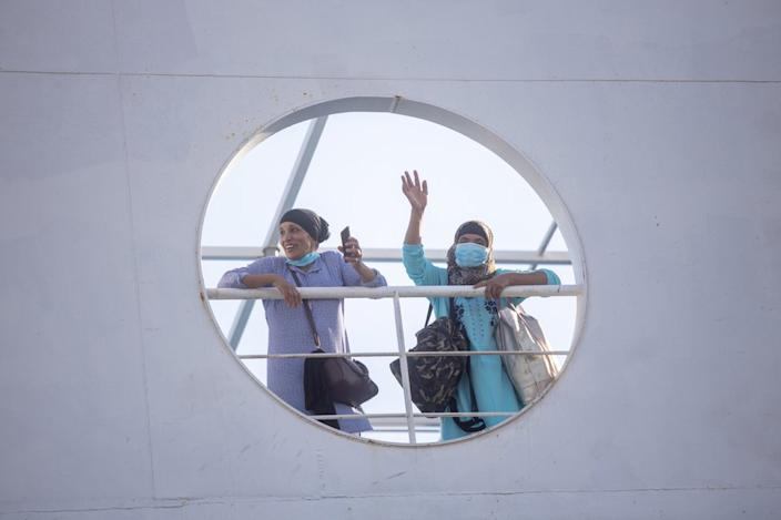 These Moroccan women wave from a boat as they return home from seasonal agricultural work in Spain - coronavirus border closures meant many workers had been stuck there since strawberry picking ended a month ago.