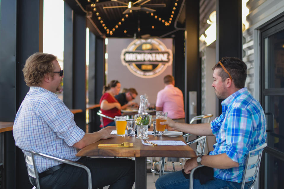 This photo provided by Adam M. Rammel shows patrons enjoying a pint at The Syndicate on Aug. 20, 2020 in Bellefontaine, Ohio. Ohio's restrictions forced Adam Rammel to at least temporarily abandon plans for a catering and event space designed for parties and that opened last month, in time for the holidays. Rather than have the space sit unused, Rammel turned it into The Syndicate, a restaurant located next door to his 5-year-old brewpub, Brewfontaine. (Susie Jarvis/Adam M. Rammel via AP)