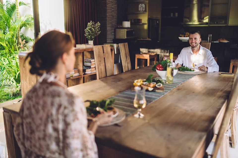 couple sitting very far from each other at large dining table